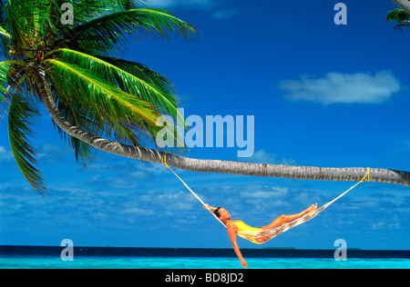 Woman relaxing in hammock handing from palm tree under warn blue skies during tropical holidays - Stock Photo