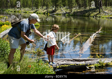 Grandfather teaching young grandson fly fishing in the headwaters of the Deschutes River near Bend, Oregon, USA - Stock Photo