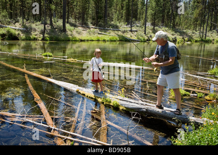 Grandfather teaching young grandson fly fishing in the Cascades near Bend, Oregon - Stock Photo
