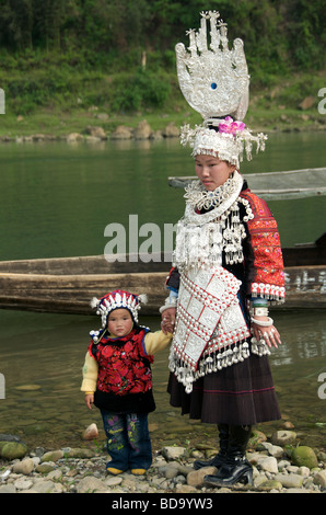 Mother and child in formal dress at riverbank posing for photos at Miao Drum Festival Shidong Guizhou Province China - Stock Photo