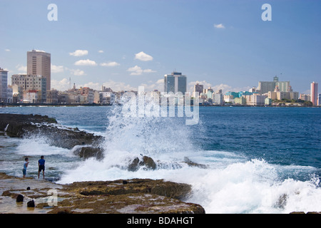 Boys play on the rocks as waves crash along the Malecon in Old Havana, hotels of Vedado are in the distance - Stockfoto