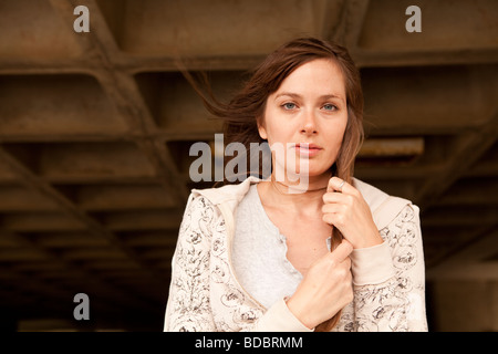 Portrait of Caucasian female brunette against waffle-like pattern of parking garage structure. - Stock Photo