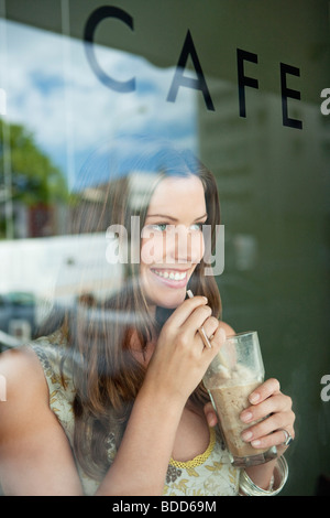 Woman drinking chocolate milkshake in a cafe - Stock Photo