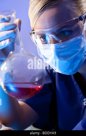 A female medical or scientific researcher or doctor looking at a flask of red liquid in a laboratory. - Stock Photo