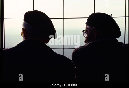 Two frenchman wearing berets share the view from the top of the Eiffel Tower in Paris, France - Stock Photo