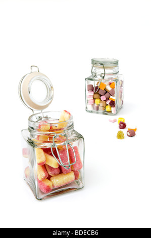 Studio shot of sweets in two glass jars against a white background - Stock Photo