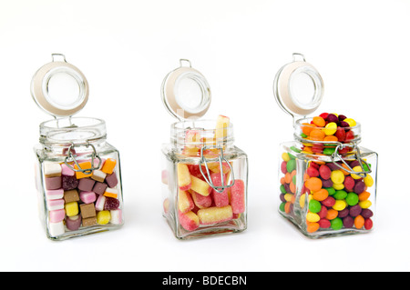 Studio shot of a mixture of sweets in three open glass jars against a white background - Stock Photo