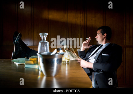 Vintage portrait of businessman smoking with feet up on desk - Stock Photo