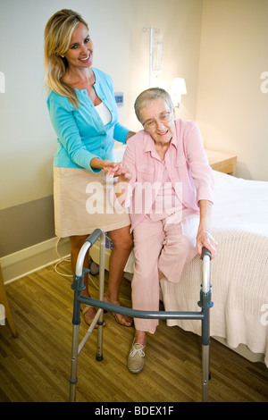 Adult daughter helping elderly mother use walker - Stockfoto