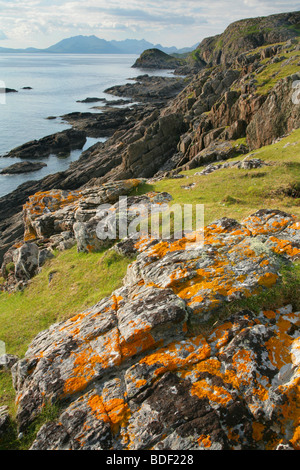 Orange lichen on rocks near the Point of Sleat looking towards the Cuillin mountains, Isle of Skye, Scotland. - Stock Photo