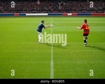 Rugby player throwing ball - Stock Photo