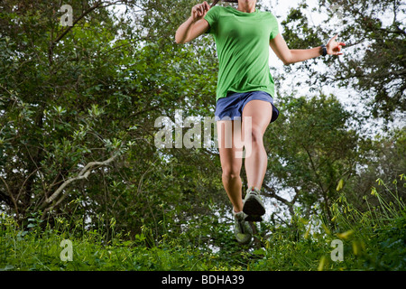View from below of a woman trail running through a green meadow in the woods. - Stock Photo