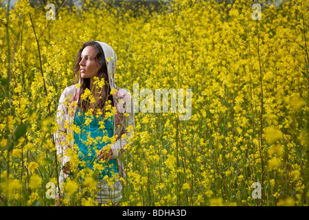 Young woman standing in a field of yellow flowers wearing a hood and looking into the distance - Stock Photo