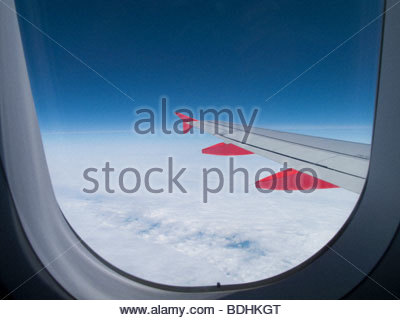 View of airplane wing in sky from window - Stock Photo
