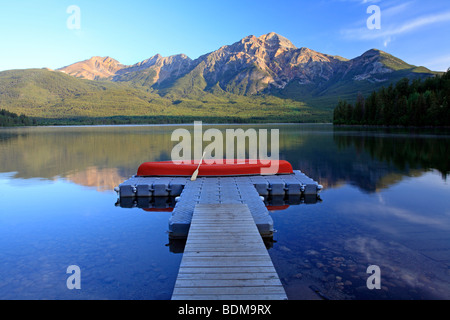 Red canoe on dock at Pyramid Lake with Pyramid mountain, Jasper National Park, Alberta, Canada. - Stock Photo