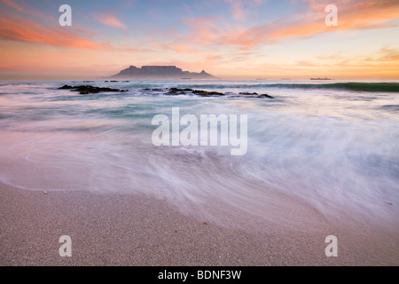 Surf on beach at Table Bay, with Table Mountain in background at sunset, Bloubergstrand, Western Cape Province, - Stock Photo