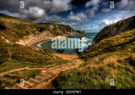 Uneven steps leading down in to Man of War bay in dorset looking out over a windy bay with white water breaking - Stock Photo