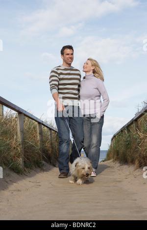 Couple walking dog on beach boardwalk - Stock Photo