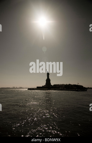 The Statue of Liberty seen from the water in New York Harbor, USA. - Stock Photo