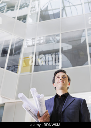 Business man holding rolled blueprints under arm in atrium of office building, low angle view - Stock Photo