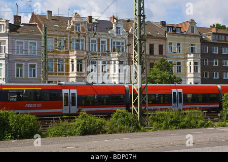 Regional train from Deutsche Bahn AG in front of Gruenderzeit buildings, from the Founder's Epoch period, in the - Stock Photo