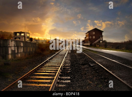 A railway track leading into the distance through a small station at sunset - Stock Photo