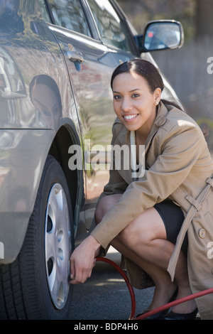 Hispanic woman inflating a tire of a car - Stock Photo
