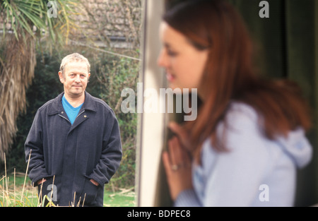 teenage girl looking out of a window at a man who is stalking her - Stockfoto