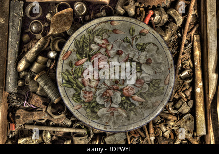 An old tin with a decorative floral design in a box of old nuts and bolts - Stock Photo