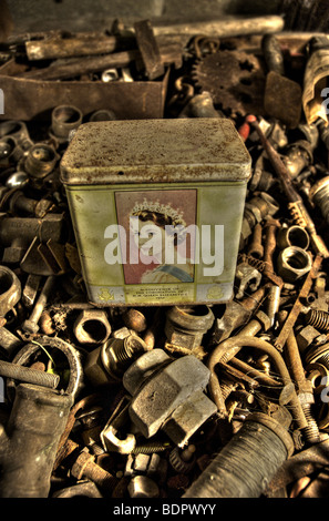An old tin with a picture of Queen Elizabeth II in a box of old nuts and bolts - Stock Photo