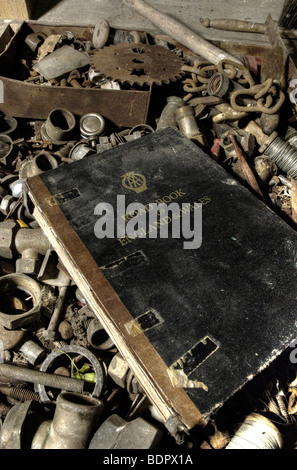 An old black book of AA road maps in a box of old nuts and bolts - Stock Photo
