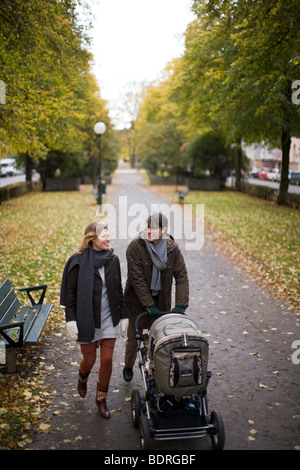 A couple taking a walk with their baby - Stock Photo