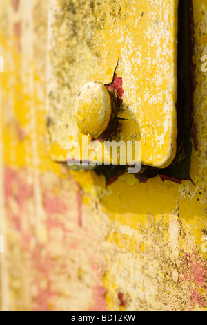 Flaking paint and metal of an antique petrol pump. - Stock Photo