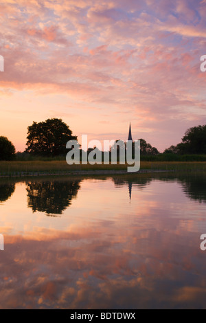 Salisbury Cathedral spire and dawn sky reflected in a pond, Salisbury, Wiltshire, England. Summer (June) 2009. - Stock Photo