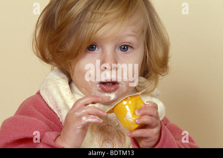 Young baby toddler child eating yogurt messily - Stock Photo