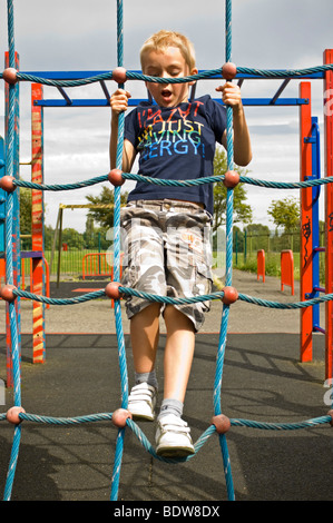 Vertical close up portrait of a young boy having great fun climbing up a cargo net on a climbing frame in a childrens - Stock Photo