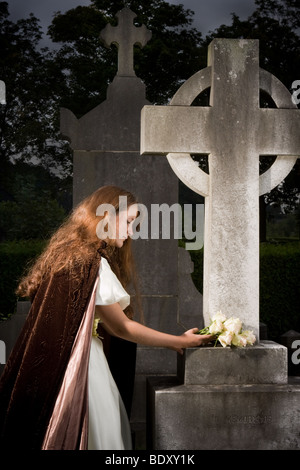 Young victorian woman putting flowers on a grave - Stock Photo