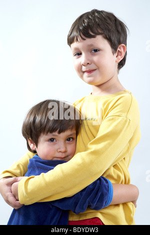 Six-year-old boy hugging his three-year-old sister - Stock Photo