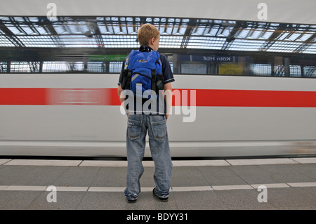 Boy, 9, standing on the platform in front of a passing ICE train, main railway station in Cologne, North Rhine-Westphalia, - Stock Photo