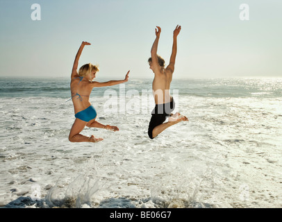 Couple leaping into waves on beach - Stock Photo