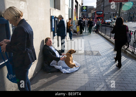 A street beggar strategically seated between two ATM machines in Borough High St, London, SE1 - Stock Photo