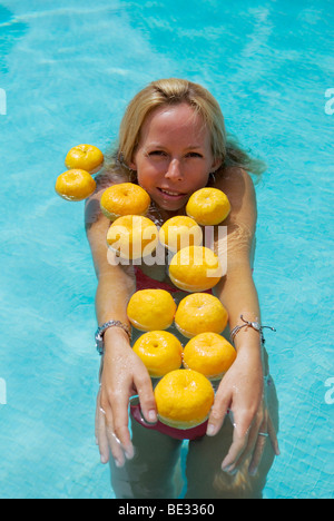 beautiful smiling young woman with long blond hair in swimming pool with floating oranges - Stock Photo