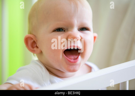 A one-year-old girl in her crib - Stock Photo