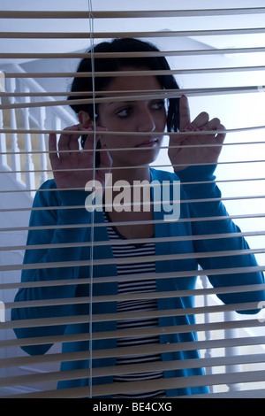 Young woman looking out of a window, - Stockfoto