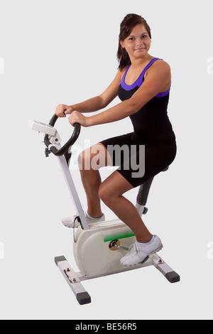 Girl on exercise bike - Stock Photo