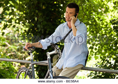 A man sitting on railings talking on a mobile phone - Stock Photo