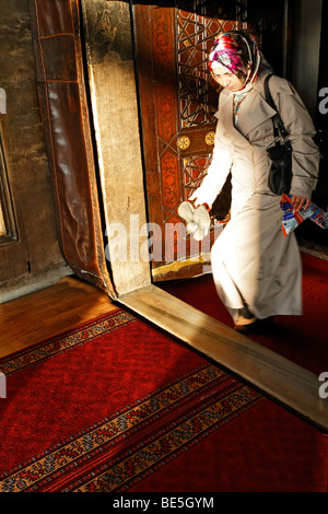 Muslim woman with headscarf exiting a mosque, shoes in hand, Ueskuedar, Istanbul, Turkey - Stock Photo