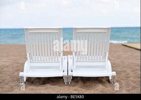Two deck chairs on a beach, near Antalya, Turkey - Stock Photo