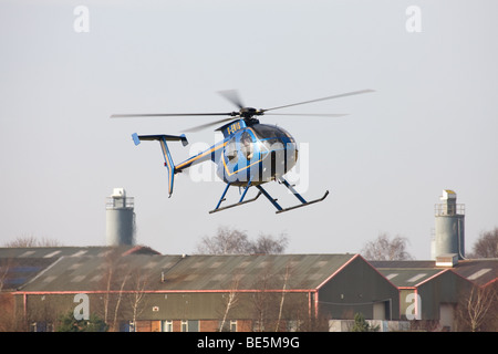 Hughes 369D 500 G-ERIS hovering prior to landing at Sandtoft Airfield - Stock Photo