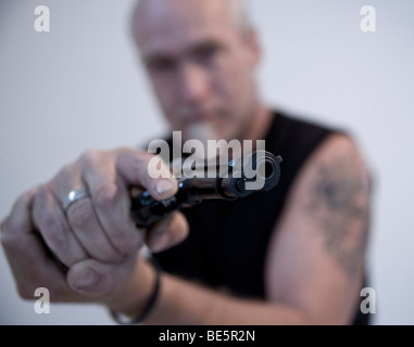 Man with a pointed beard and a tattoo on the upper arm, holding a gun - Stock Photo